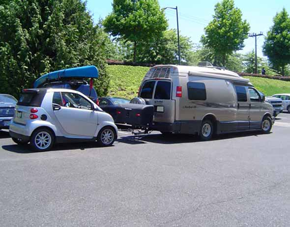 Travel van with StowAway Standard Cargo Carrier towing a Smart car